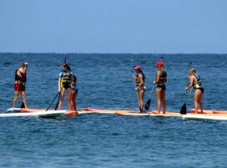 summer campers paddle boarding