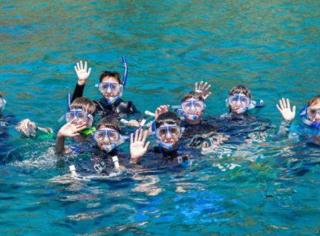 snorkelers in ocean waving at camera