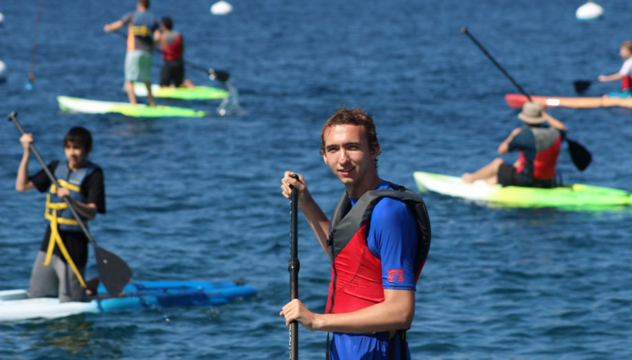 camper looking at the camera while stand up paddleboarding and other campers in the background