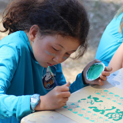 camper painting during arts and crafts time