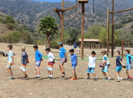 boys in a line with their hands behind their back in a challenge activity