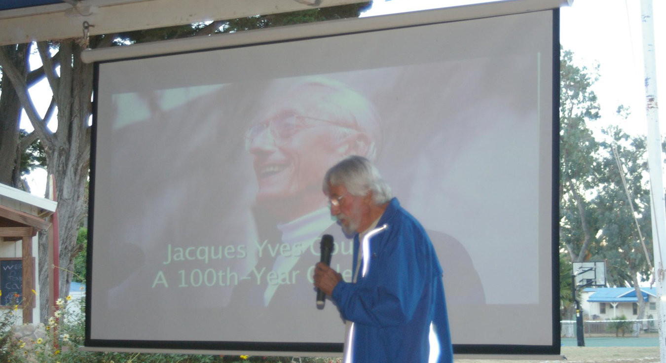 Jean-Michele Cousteau giving a presentation in front of a projector screen