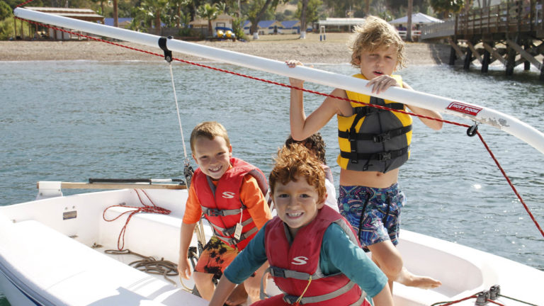 kids in life jacket on boat