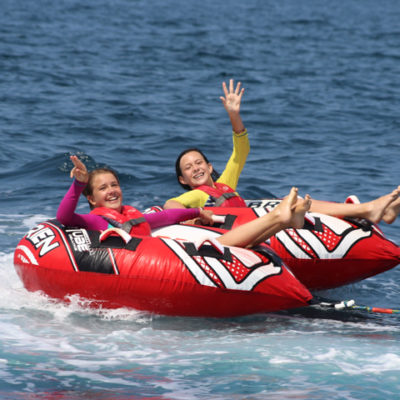 Two campers being pulled in a tube by a powerboat