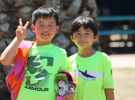 two campers smiling for a photo in green shirts with their towels and water bottles