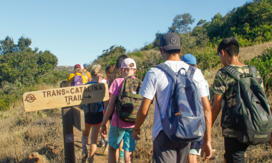 campers hiking past a direction sign