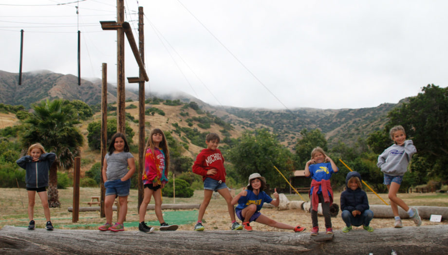 kid posing for a photo on top of a log by the ropes course