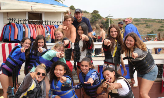 counselors and campers posing for a photo with lifejackets on by the dock