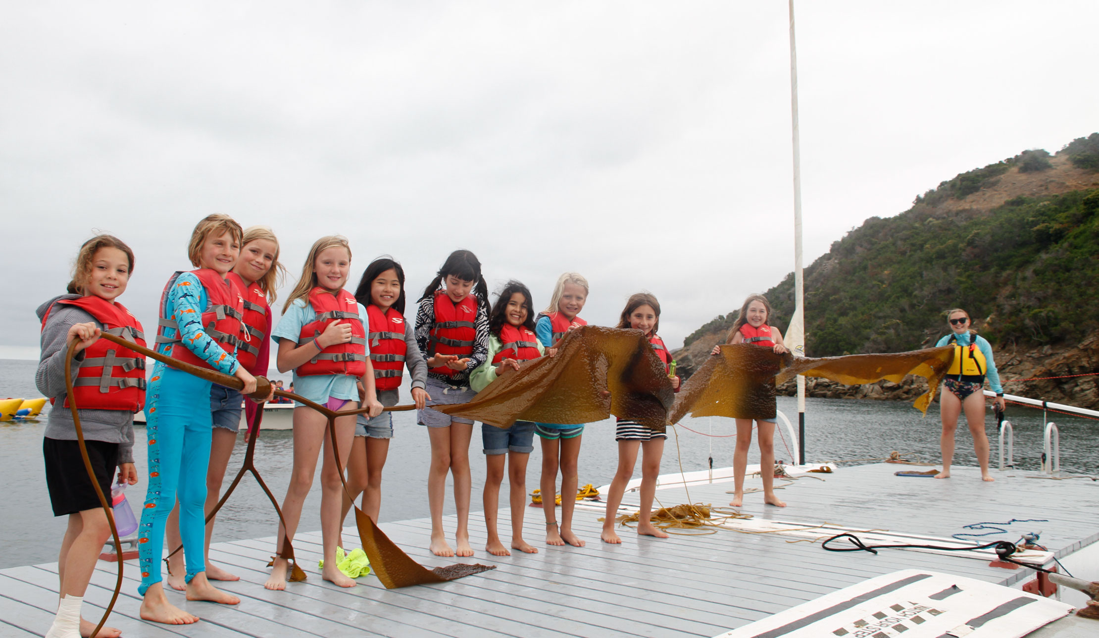 girls on the dock wearing lifejackets with a counselor holding a very long piece of kelp