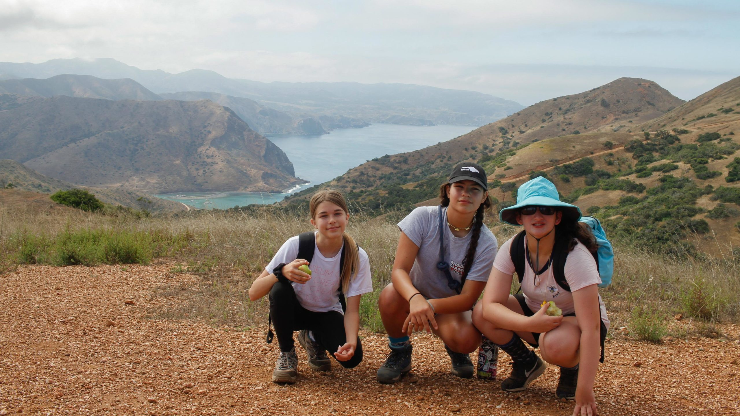 summer campers kneeling and overlooking the catalina island landscape